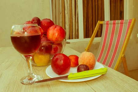 Beautiful sweet peaches, nectarine and plums. Ripe fruit on the table. A glass of red wine - Retro color Stock Photo