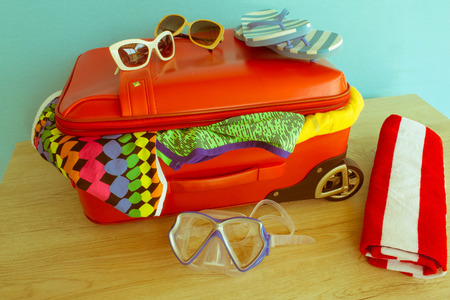 Suitcase with different things prepared for travel. Red suitcase with clothes and personal things packed for travelling - Retro color