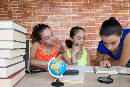 Três raparigas que trabalham em sua lição de casa. Pensamentos, educação, conceito de criatividade Foto de archivo - 89288521