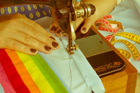 processes of sewing on the sewing machine sew womens hands sewing machine. Female tailor threading leather material on sewing machine Stock Photo