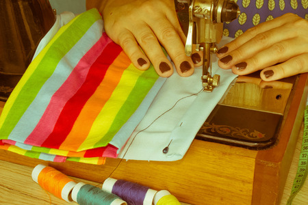 closeup of woman hands sewing yellow cloth outdoors. Womans Hand Sewing Quilt