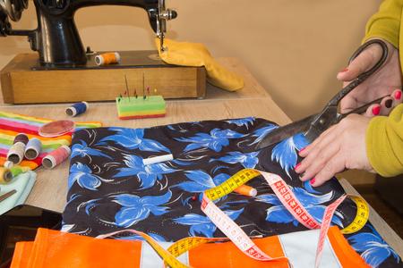 Tailor Woman, fashion designer working at studio. Fashion designer cutting textile next to a sewing machine