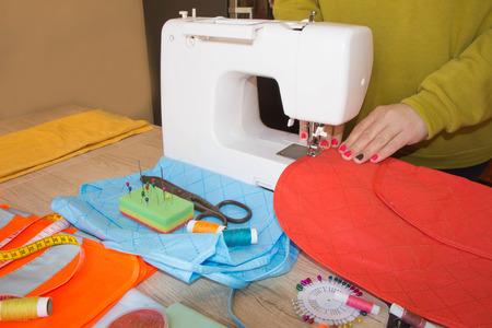 Woman hand on sewing machine. Dressmaker work on the sewing machine. Hobby sewing fabric as a small business concept. Female fashion designer working