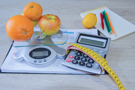 Concept of diet. Low-calorie fruit diet. Diet for weight loss. Measuring tape and fruits on the table. Vegetarian diet for weight loss. Fruit diet. Low-fat diet Stock Photo