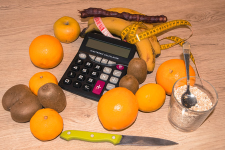 Fruits, calculator and centimeter on a wooden table. Diet concept