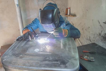 Welder argon welding for aluminum at work. Man welds aluminum