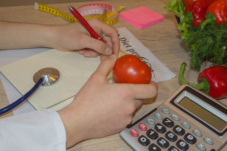 Young female nutritionist working in her office. Female nutritionist hand writing diet plan in notebook against fresh vegetable composition Stock Photo