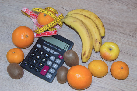 Concept of diet. Low-calorie fruit diet. Diet for weight loss. Plate with measuring tape and fruits on the table. Vegetarian diet for weight loss