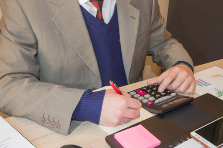 Hand with calculator. Finance and accounting business. Young Businessman Calculating Finance Bills In Office. Pen on paperwork accounts with man use computer to save data in background