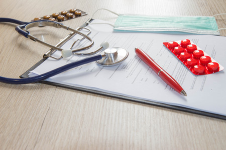 Overhead shot of medical equipment on wooden table. Doctor desk and medical equipment