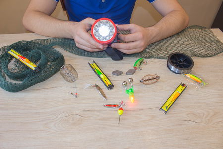 spinner with a Accessories for fishing in the hand. bait, wobbler and fishing accessories on the table 写真素材