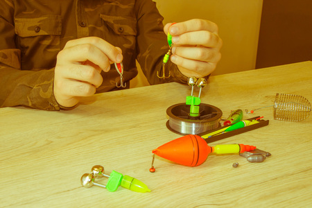 spinner with a triple hook for fishing in the hand. Fishing equipment on the table 写真素材