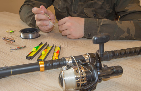 Composition with accessories for fishing on a wooden background. Close-up of a fisherman's hands with Fishing tackle
