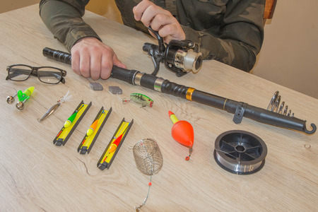 Close-up of a fishermans hands with Fishing tackle.  Items include fishing reel, hooks, floats