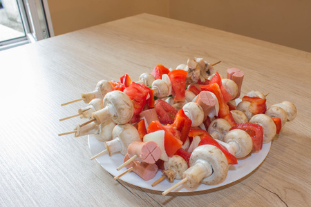 delicious kebabs with vegetables. mushrooms and sausages on skewers on a plate. Champignon process with ingredients