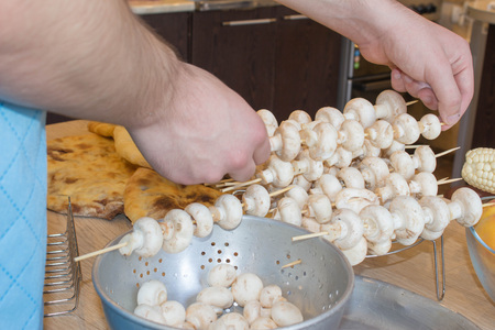 A man hand puts pieces of mushrooms on skewer. mushrooms on skewers. process of cooking a delicious mushrooms