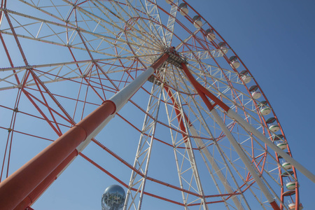 A ferris wheel in the park in Batumi. Brightly colored Ferris wheel against the blue sky