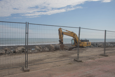 Building a dike. Excavator put stones in the sea. excavator builds a beach on the sea shore