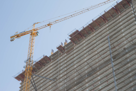 Construction site. Big industrial tower crane with unfinished high raised building