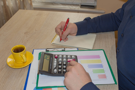 Businessman using a calculator to calculate the numbers. Businessman calculate finance and thinking about problem in home office Imagens