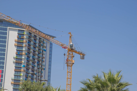 Tower crane against the building under construction. Construction of a new district. Lifting crane build multi-storey buildings Stockfoto