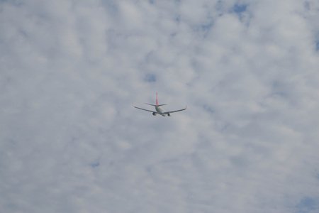 Passenger airplane fly on a hight above overcast clouds and blue sky. The plane of was flying at the airport