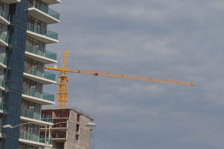 Construction site background. A crane in a construction work. Building crane. Lifting crane build multi-storey building
