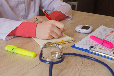 Doctor Writing application form, just hands at the table. Medical and Health care concept