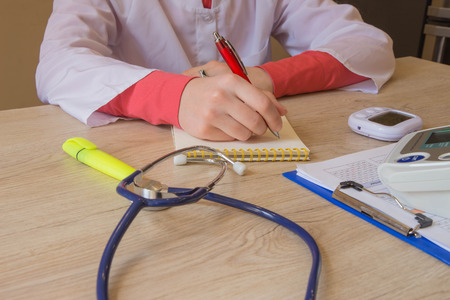 Medicine doctor's working table. Healthcare and medical concept. Female medical doctor writing something sitting at her office