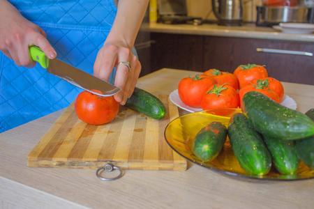 Les mains de la femme coupant des légumes, derrière des légumes frais. Femme cuisinier à la cuisine. Nourriture saine Banque d'images