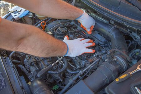 Close up hands of unrecognizable mechanic doing car service and maintenance. Auto Repair and care Concept