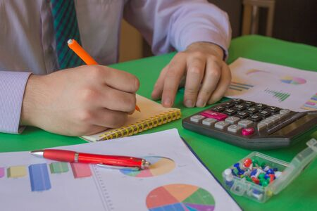 Businessman calculating the financial statements. Close up young man with calculator counting making notes at home. man working in a office