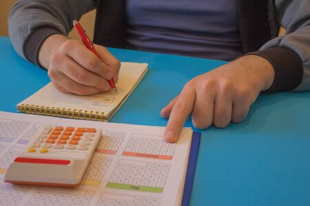 Savings, finances, economy, Business and home concept - man with calculator counting money and making notes at home. Business and finances concept