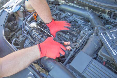 Worker repairs a car in a car repair center. Repair service. Maintenance of automotive. The mechanic is repairing the car 스톡 콘텐츠