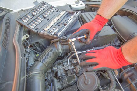car service, repair, maintenance and people concept - auto mechanic man with wrench working at workshop