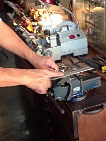 hone: Locksmith hone keys by hand Stock Photo