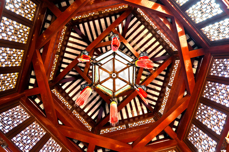 tassles: Geometric pattern of a chinese lantern hanging from wooden beams on the ceiling of a Chinese gazebo.