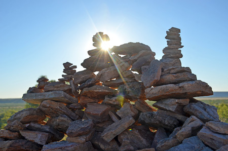 the outback: Sun flare through rock cairns (man-made stone stacks) in outback Queensland, Australia