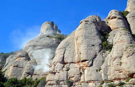abseil: Workmen abseiling, suspended from and drilling the sides of the mountains of Montserrat, Catalonia, Spain Stock Photo