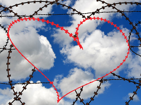 entrapment: Natural heart shape (digitally coloured red) in a barbed wire fence on sky background. Love, freedom, peace, hope and compassion concepts.