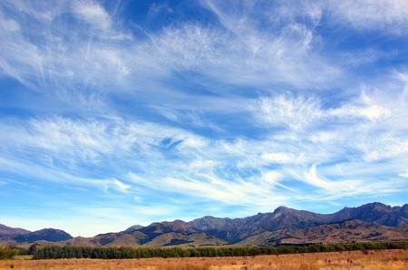 wispy: Wispy clouds in blue skies above a rugged mountain range, near Dunedin, New Zealand Stock Photo