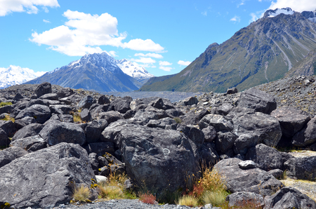 aoraki mount cook national park: Scree slope and boulder fields at the base of a snow covered rocky mountain range in Mount Cook (Aoraki) National Park, New Zealand