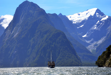 Tall ship on Milford Sound, in fiordland, Southern Alps, New Zealand, is dwarfed by the height of the mountains.