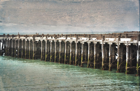 oamaru: Historic wooden Sumpter Wharf at Oamaru Harbour, New Zealand. Vintage, grunge textured image. Roosting site for colony of shags (waterbirds).