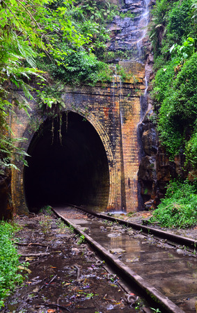 Water cascading across the entrance to an historic abandoned railway tunnel in Helensburg, New South Wales, Australia Stock Photo