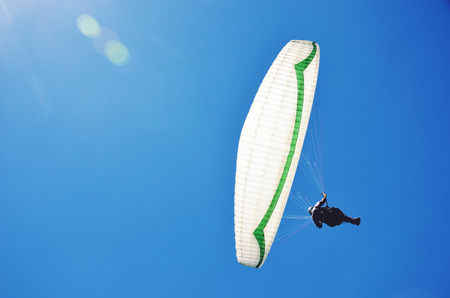View from below of a paraglider soaring through clear blue sky. Copy space for text. Stanwell Tops, New South Wales, Australia.