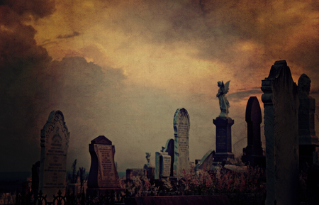 portent: Gothic cemetery landscape at twilight with old headstones and angels under a dramatic, sky. Vintage grunge textured image. Selective focus with copy space for text.