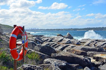 Los salvavidas suenan en plataformas de la roca en la costa costa rocosa con las ondas de fractura y el horizonte de la ciudad de Sydney en el fondo, Nuevo Gales del Sur, Australia. Foto de archivo - 76997317