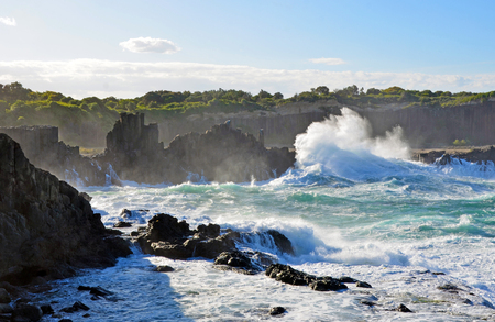 Rough seas and big swell breaking over basalt column rock formations at Bombo Headland quarry, New South Wales coast, Australia