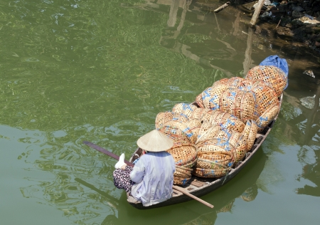 non la: Woman in boat full of baskets, Hoi An, Vietnam Stock Photo